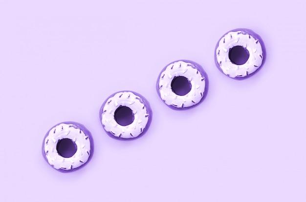 Viele kleinen plastikschaumgummiringe liegen auf einem bunten pastellhintergrund.