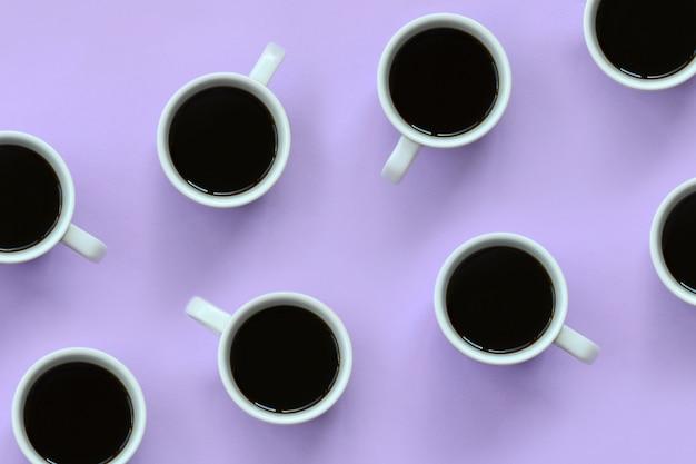 Viele kleinen weißen kaffeetassen auf beschaffenheitshintergrund der violetten pastellfarbe der mode