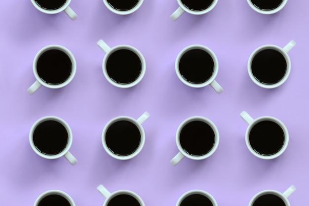 Viele kleinen weißen kaffeetassen auf beschaffenheitshintergrund des violetten farbpastells der mode im minimalen konzept