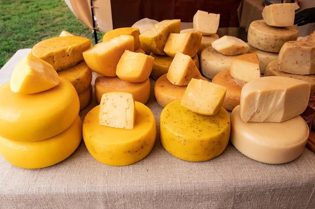 Viele köpfe von natürlichem bauernkäse verschiedener sorten, die nach traditioneller technologie hergestellt wurden, liegen auf dem tisch