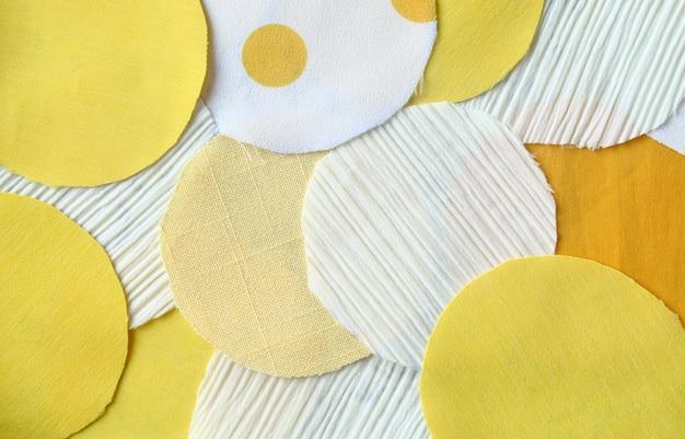 Viele kreisen gelbes und weißes lappengewebe für hintergrund ein