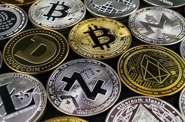 Viele kryptowährungs-münzen liegen auf einer dunklen oberfläche