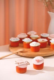 Viele leckere cupcakes. valentinsgruß süßer liebescupcake auf dem tisch auf hellem hintergrund