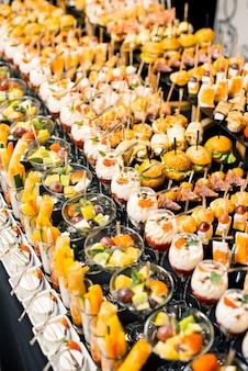 Viele leckere desserts und aperitifs auf einem partytisch.