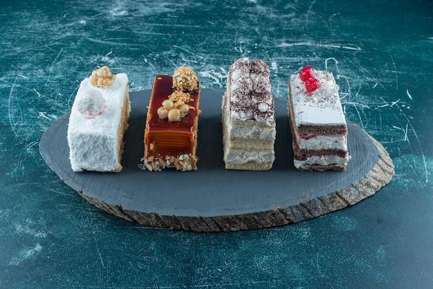 Viele leckere kuchenstücke auf einem holzbrett. hochwertiges foto