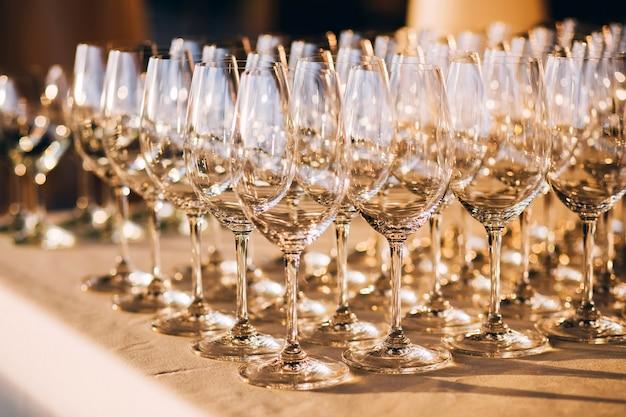 Viele leere champagnergläser schließen sich. glasbecher auf dem weißen tisch. leeres kristallweinglas. glasbecher auf einem hohen bein.
