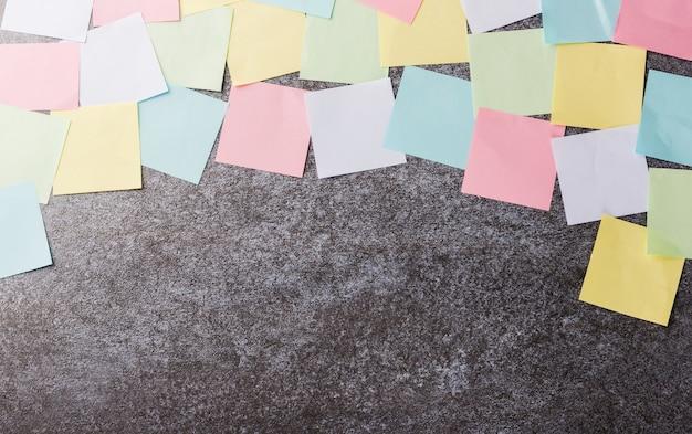 Viele leere mehrfarbige papier-haftnotizenliste auf betonwand