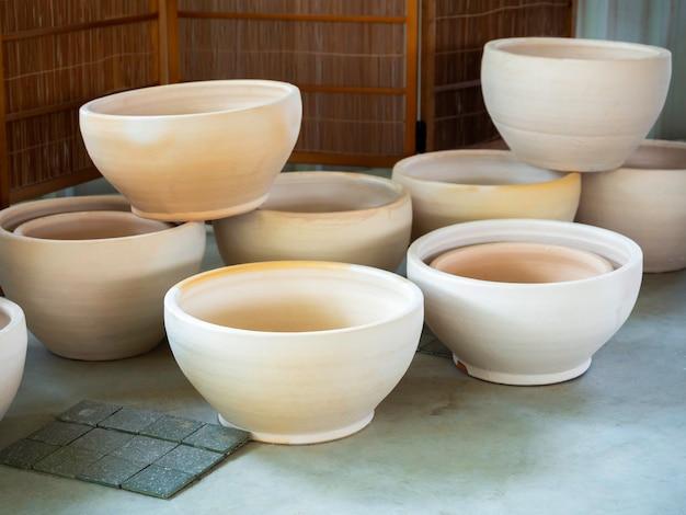 Viele leere runde weiße keramikpflanzentöpfe auf betonboden angeordnet. leerer keramiktopf.
