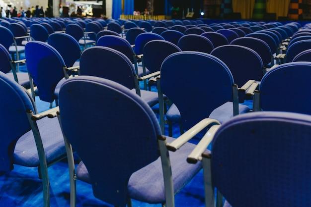 Viele leeren blauen reihenstühle in einem theater.