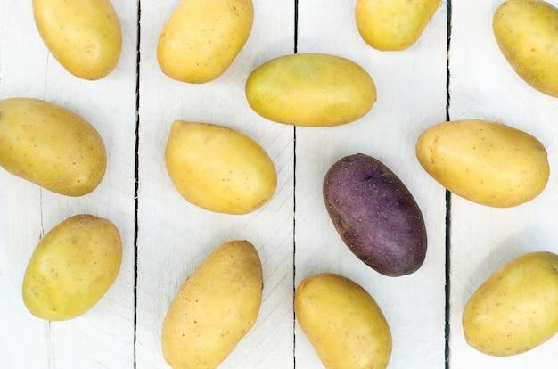 Viele leichte kartoffeln und eine lila kartoffel auf einem weißen hölzernen hintergrund