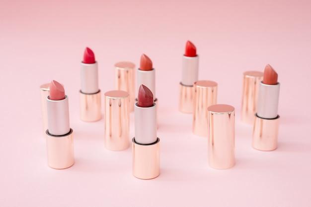 Viele luxusgoldlippenstifte in den verschiedenen schatten des rosas stehen auf einem rosa pastellhintergrund