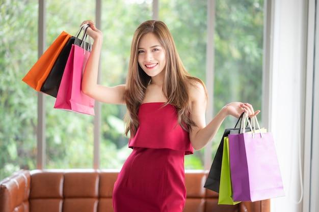 Viele mädchen sind shopaholics wie sie. sie ist schön im roten kleid und hält einkaufen b
