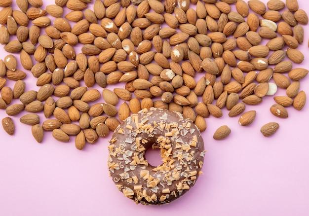 Viele mandeln und süßer donut auf rosa hintergrund. ansicht von oben