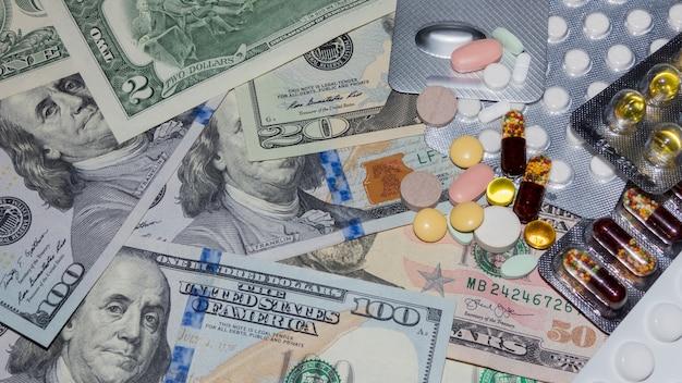 Viele medizinische pillen in verschiedenen farben auf dollarnoten, ansicht von oben