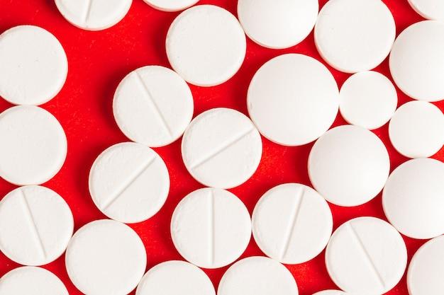 Viele medizinpillen auf rotem hintergrund