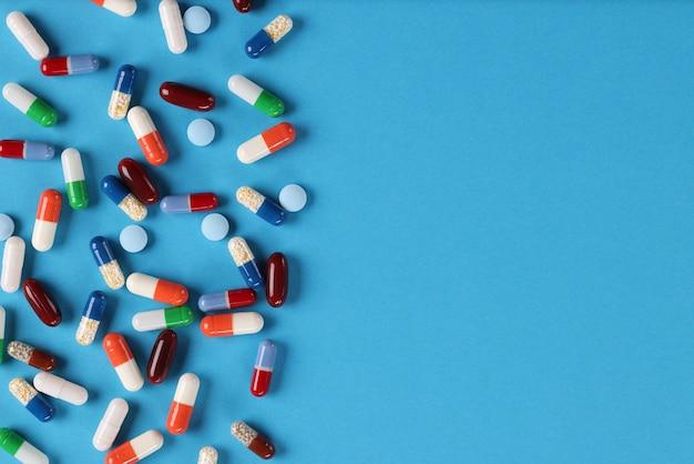 Viele mehrfarbige medizinische kapseln und pillen liegen auf blauem hintergrund