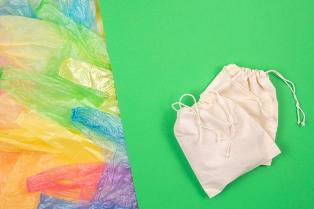 Viele mehrfarbige plastiktüten mit einer natürlichen wiederverwendbaren öko-tasche zum einkaufen auf grün.