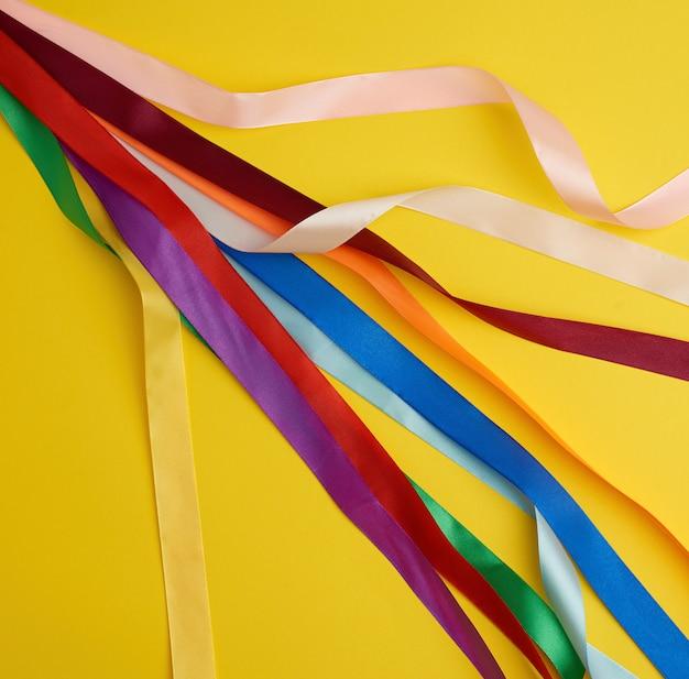 Viele mehrfarbige seidenbänder auf gelb