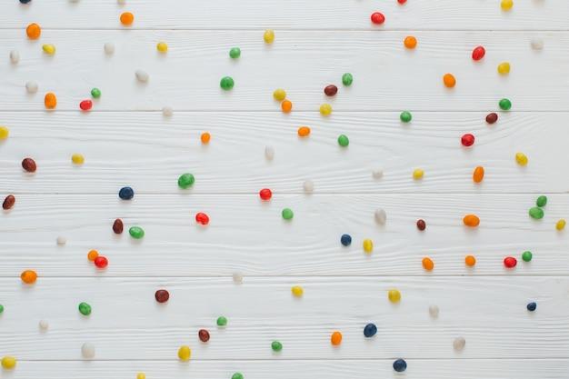 Viele mehrfarbige süße süßigkeiten auf weißem hölzernem hintergrund.