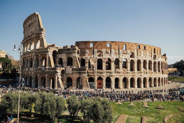 Viele menschen spazieren um das kolosseum, die antike stadt rom.