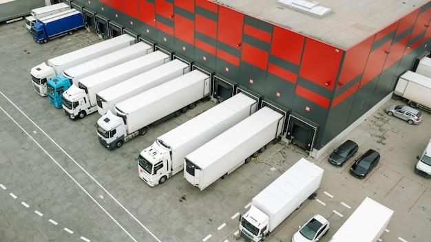Viele möglichkeiten, waren und fracht des welthandels zu transportieren, lkws in einem logistiklager zu beladen, lieferung aus einem online-shop
