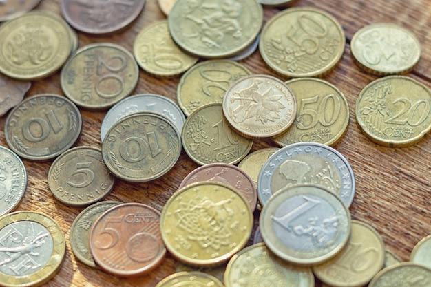 Viele münzen auf der holzoberfläche