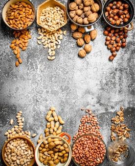Viele nüsse in verschiedenen schalen auf rustikalem hintergrund