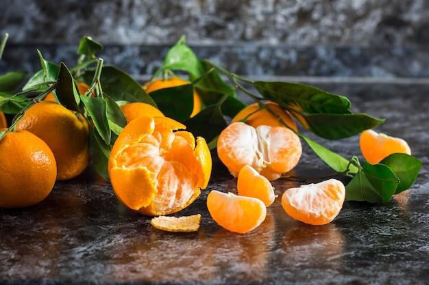 Viele orange mandarinen mit grünen blättern auf dunklem hintergrund. geschälte mandarinenscheiben