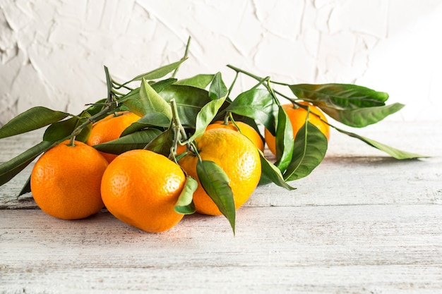 Viele orange mandarinen mit grünen blättern auf weißem holzhintergrund