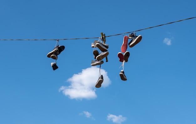 Viele paar sportschuhe hingen an einem seil vor blauem himmel.