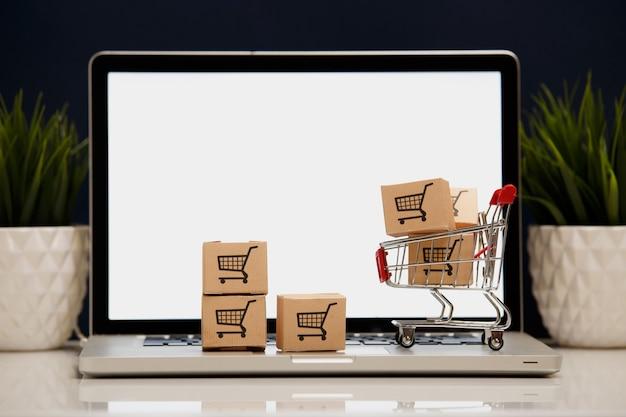 Viele papierboxen in einem kleinen einkaufswagen auf einer laptoptastatur konzepte über online-einkäufe, dass verbraucher dinge direkt von zu hause oder im büro mit nur wenigen klicks über den webbrowser kaufen können