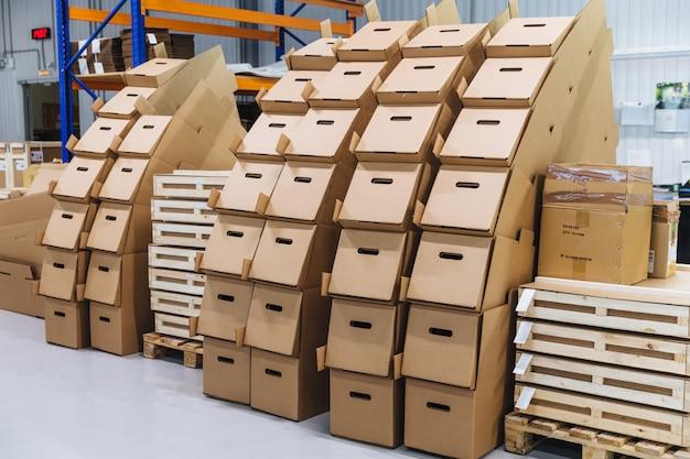 Viele papierkästen gegen lagerhausinnenraum. pappe eingepackt im industrielagerspeicher