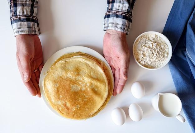 Viele pfannkuchen sind auf einem weißen teller gestapelt.