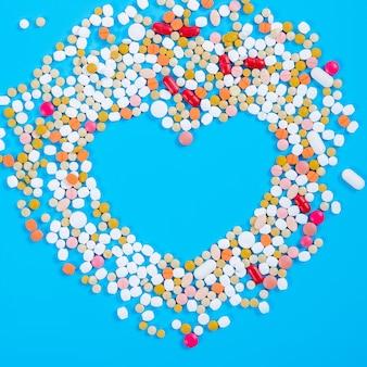 Viele pillen in form eines herzens mehrfarbig auf blauem grund