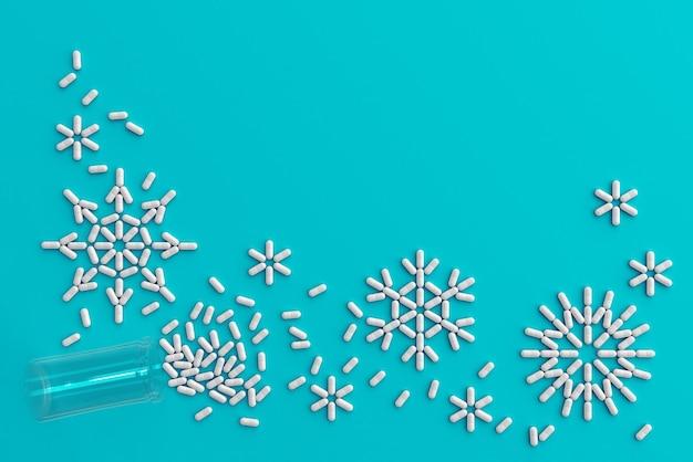 Viele pillen verstreut auf einem blauen hintergrund in form von schneeflocken und figuren 2020. 3d-illustration