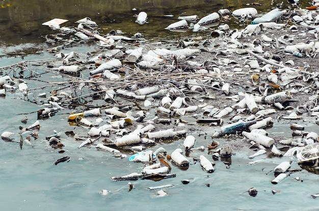 Viele plastik- und glasflaschen am grund der flussverschmutzung