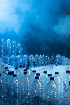 Viele plastikflaschen und rauch, verschmutzungsquelle. konzept des recyclings von kunststoff und ökologie.
