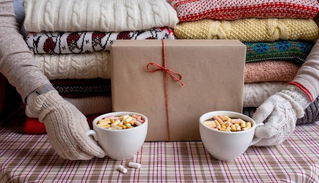 Viele pullover und pullover in verschiedenen farben in zwei haufen und händen mit zwei tassen kaffee gefaltet.