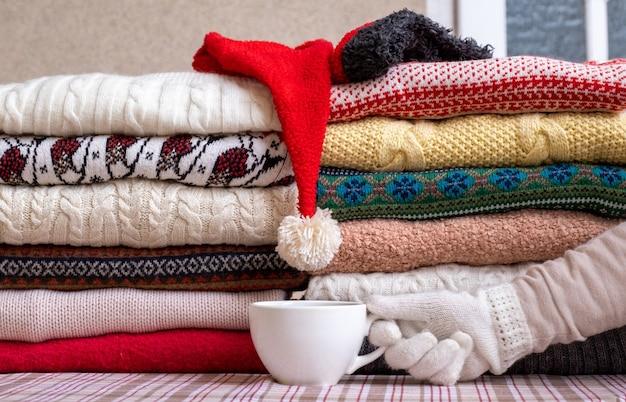 Viele pullover und pullover in verschiedenen farben, in zwei stapel gefaltet und mit einer tasse kaffee versehen.