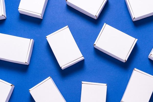 Viele quadratische kartonschachteln auf blauem hintergrund