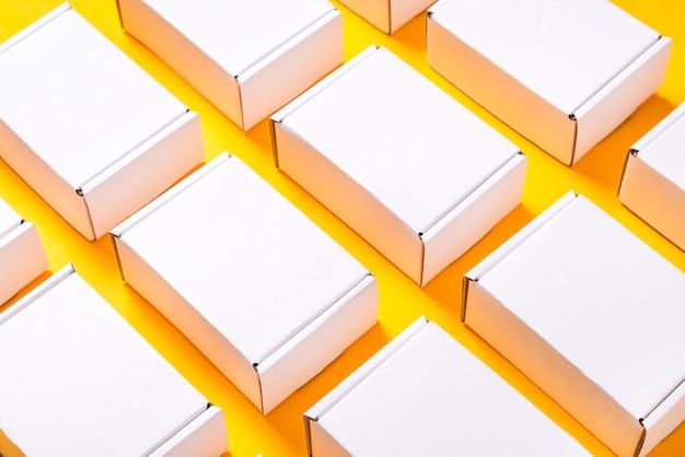 Viele quadratische kartonschachteln auf gelbem hintergrund
