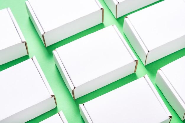 Viele quadratische kartonschachteln auf grünem hintergrund