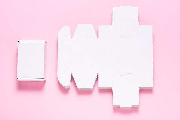 Viele quadratische kartonschachteln auf rosa hintergrund, geschnitten