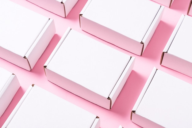 Viele quadratische kartonschachteln auf rosa hintergrund
