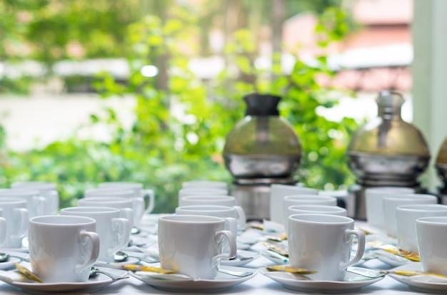 Viele reihen der weißen kaffeetasse mit untertasse und teelöffel auf tabelle und kaffeemaschine