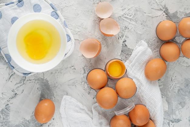 Viele rohen ungekochten hühnereien in einer kunststoffschale auf der schmutztabelle, spezielle eidiäten