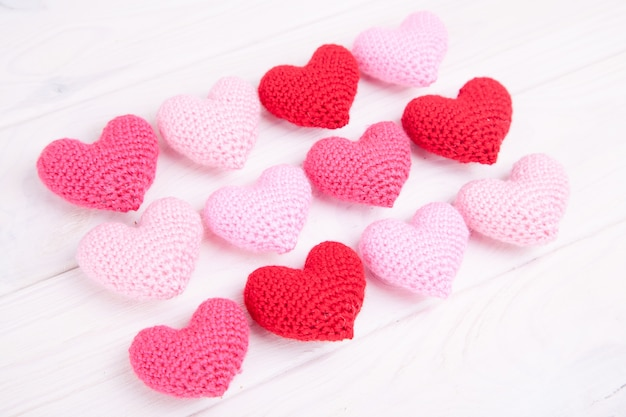 Viele rosa gestrickten herzen auf einem weißen hölzernen hintergrund. valentinstag.