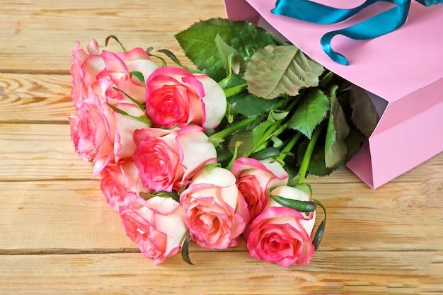 Viele rosa rosen in der gegenwärtigen papiertüte auf holz