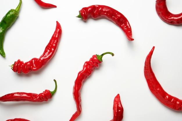 Viele rote ganze früchte von paprika und eine grüne auf einem weißen