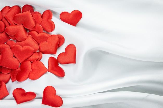 Viele rote herzen auf einem faltigen weißen hintergrund